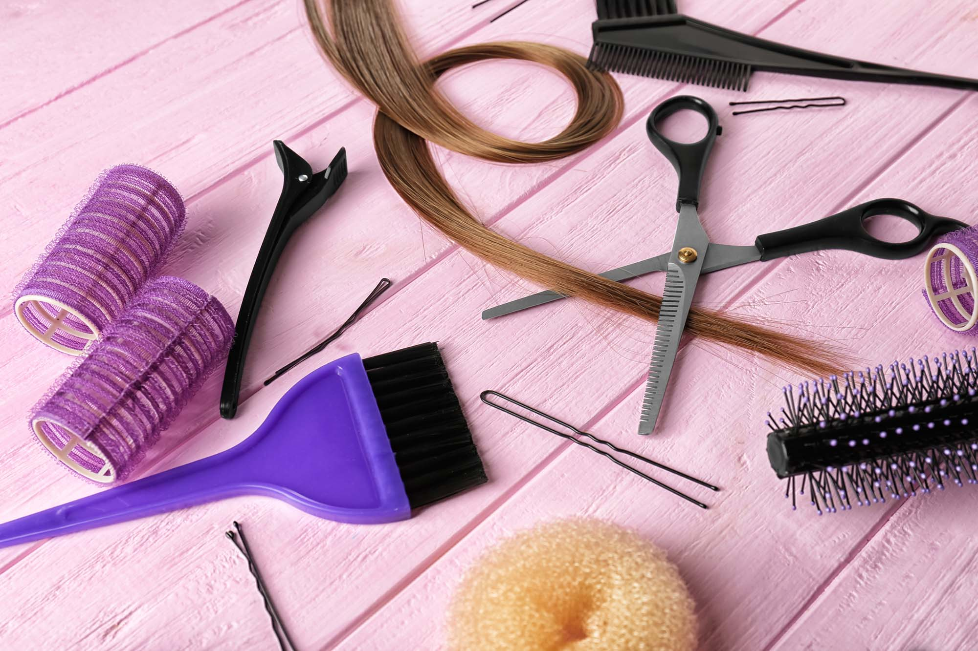 Set of hairdresser's supplies on color wooden background